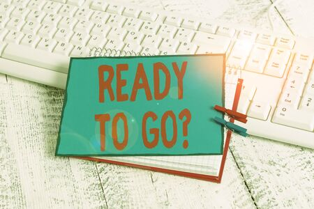 Handwriting text Ready To Go Question. Conceptual photo asking someone if he is prepared or packed his things notebook paper reminder clothespin pinned sheet white keyboard light wooden