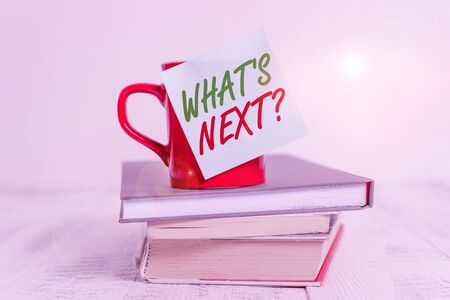 Conceptual hand writing showing What S Next Question. Concept meaning asking demonstrating about his coming actions or behaviors Coffee cup sticky note stacked books retro old retro wooden table