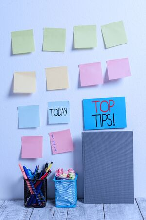 Conceptual hand writing showing Top Tips. Concept meaning small but particularly useful piece of practical advice Sticky Notes Card on Wall Pencil Pots Notebook on Work Desk