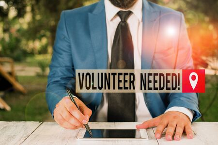 Word writing text Volunteer Needed. Business photo showcasing asking demonstrating to work for organization without being paid Businessman holds pen and points into copy space Stock fotó