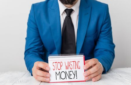 Writing note showing Stop Wasting Money. Business concept for advicing demonstrating or group to start saving and use it wisely Man holds empty paper with copy space in front of him Space