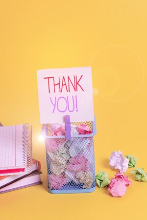 Handwriting text writing Thank You. Conceptual photo polite expression used when acknowledging gift service compliment Trash bin crumpled paper clothespin empty reminder office supplies yellow