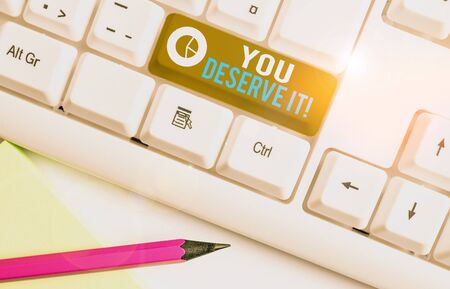 Escritura a mano conceptual mostrando que te lo mereces. Concepto Significado debe tenerlo debido a sus cualidades o acciones Teclado de pc blanco con papel de nota sobre el fondo blanco. Foto de archivo