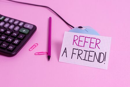 Handwriting text Refer A Friend. Conceptual photo direct someone to another or send him something like gift Wire mouse clips marker calculator squared paper sheet colored background