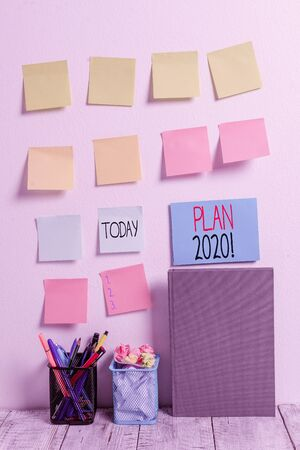 Conceptual hand writing showing Plan 2020. Concept meaning detailed proposal doing achieving something next year Sticky Notes Card on Wall Pencil Pots Notebook on Work Desk