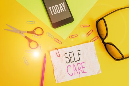 Conceptual hand writing showing Self Care. Concept meaning the practice of taking action to improve one s is own health Paper sheets smartphone scissors eyeglasses colored background Stock fotó