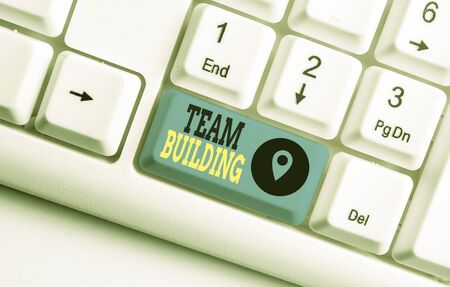 Conceptual hand writing showing Team Building. Concept meaning various types of activities used to enhance social relations White pc keyboard with note paper above the white background