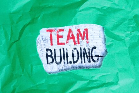 Conceptual hand writing showing Team Building. Concept meaning various types of activities used to enhance social relations Green crumpled colored paper sheet torn colorful background