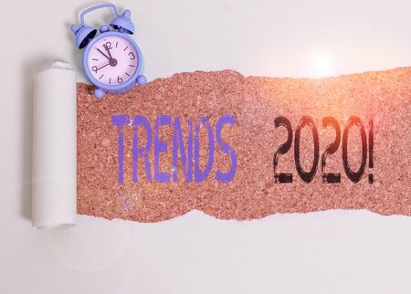 Word writing text Trends 2020. Business photo showcasing general direction in which something is developing or changing Alarm clock and torn cardboard placed above a wooden classic table backdrop