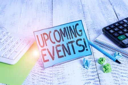 Text sign showing Upcoming Events. Business photo showcasing the approaching planned public or social occasions Notepaper stand on buffer wire in between computer keyboard and math sheets