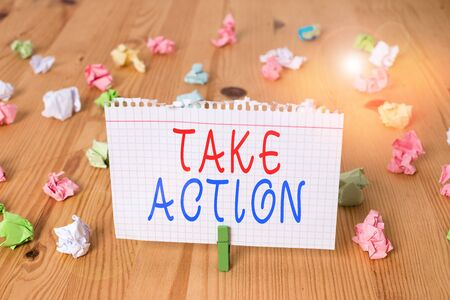 Text sign showing Take Action. Business photo text to do somethingoract in order to get a particular result Colored crumpled papers empty reminder wooden floor background clothespin