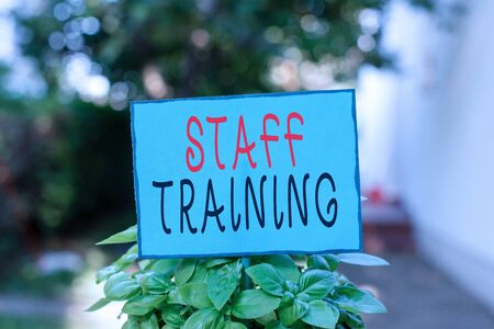 Text sign showing Staff Training. Business photo text program that helps employees learn specific knowledge Plain empty paper attached to a stick and placed in the green leafy plants