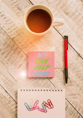 Conceptual hand writing showing We Can Help You. Concept meaning offering good assistance to customers or friends Stationary placed next to a coffee cup above wooden table Standard-Bild