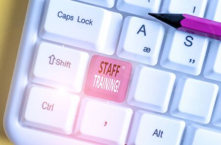 Writing note showing Staff Training. Business concept for program that helps employees learn specific knowledge White pc keyboard with note paper above the white background