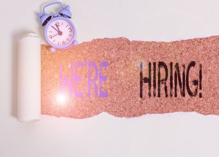 Word writing text We Re Hiring. Business photo showcasing recently employ someone or pay someone to do particular job Alarm clock and torn cardboard placed above a wooden classic table backdrop
