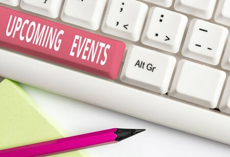 Text sign showing Upcoming Events. Business photo text the approaching planned public or social occasions White pc keyboard with empty note paper above white background key copy space Фото со стока