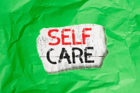 Conceptual hand writing showing Self Care. Concept meaning the practice of taking action to improve one s is own health Green crumpled colored paper sheet torn colorful background Stock fotó