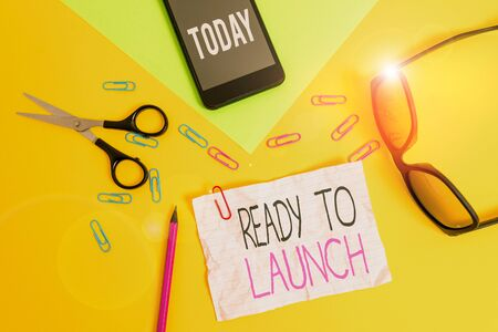 Conceptual hand writing showing Ready To Launch. Concept meaning an event to celebrate or introduce something new to market Paper sheets smartphone scissors eyeglasses colored background Фото со стока