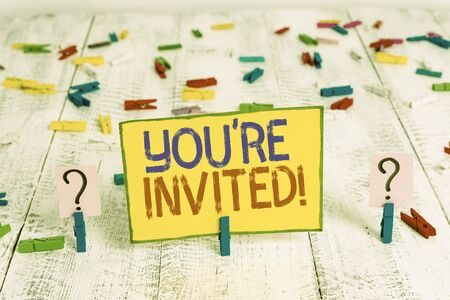 Text sign showing You Re Invited. Business photo text make a polite friendly request to someone go somewhere Scribbled and crumbling sheet with paper clips placed on the wooden table