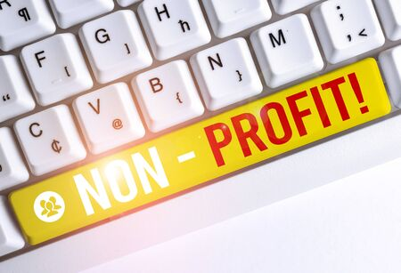 Word writing text NonProfit. Business photo showcasing not making or conducted primarily to make profit organization White pc keyboard with empty note paper above white background key copy space