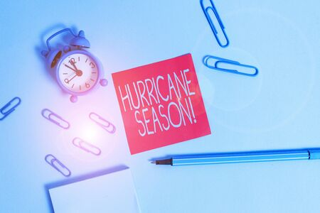 Conceptual hand writing showing Hurricane Season. Concept meaning time when most tropical cyclones are expected to develop Alarm clock notepad sticky note marker colored background