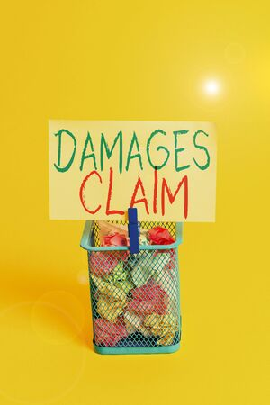 Handwriting text Damages Claim. Conceptual photo Deanalysisd Compensation Litigate Insurance File Suit Trash bin crumpled paper clothespin empty reminder office supplies yellow