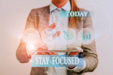 Word writing text Stay Focused. Business photo showcasing Be attentive Concentrate Prioritize the task Avoid distractions Female human wear formal work suit presenting presentation use smart device Stok Fotoğraf