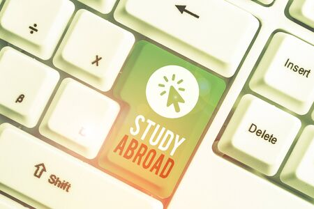 Writing note showing Study Abroad. Business concept for Pursuing educational opportunities in a foreign country White pc keyboard with note paper above the white background Фото со стока