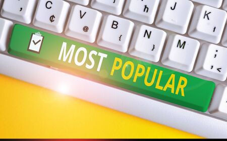 Handwriting text writing Most Popular. Conceptual photo Liked Followed Enjoyed by majority of the showing in a society White pc keyboard with empty note paper above white background key copy space 스톡 콘텐츠