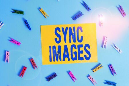 Handwriting text Sync Images. Conceptual photo Making photos identical in all devices Accessible anywhere Colored clothespin rectangle shaped reminder paper light blue background