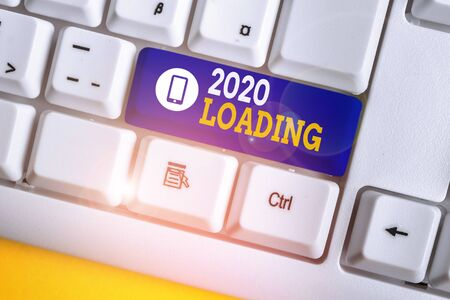 Handwriting text 2020 Loading. Conceptual photo Advertising the upcoming year Forecasting the future event White pc keyboard with empty note paper above white background key copy space 版權商用圖片 - 132647901