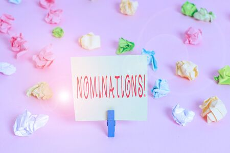 Writing note showing Nominations. Business concept for action of nominating or state being nominated for prize Colored crumpled papers empty reminder pink floor background clothespin