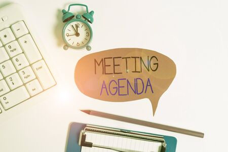 Word writing text Meeting Agenda. Business photo showcasing items that participants hope to accomplish at a meeting Flat lay above table with clock pc keyboard and copy space note paper