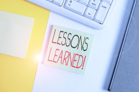 Text sign showing Lessons Learned. Business photo showcasing experiences distilled project that should actively taken Empty blank paper with copy space and pc keyboard above orange background table Stock Photo