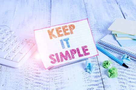 Text sign showing Keep It Simple. Business photo showcasing to make something easy to understand and not in fancy way Notepaper stand on buffer wire in between computer keyboard and math sheets 写真素材