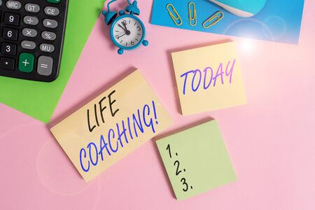 Text sign showing Life Coaching. Business photo showcasing demonstrating employed to help showing attain their goals in career Wire mouse portable calculator notepads paper sheets clips color background