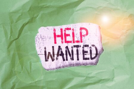 Conceptual hand writing showing Help Wanted. Concept meaning An ad in the paper an employer places to find a new employee Green crumpled colored paper sheet torn colorful background