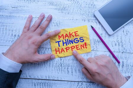 Word writing text Make Things Happen. Business photo showcasing you will have to make hard efforts in order to achieve it Hand hold note paper near writing equipment and modern smartphone device Banco de Imagens