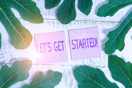 Word writing text Let S Get Started. Business photo showcasing encouraging someone to begin doing something Leaves surrounding notepaper above a classic wooden table as the background