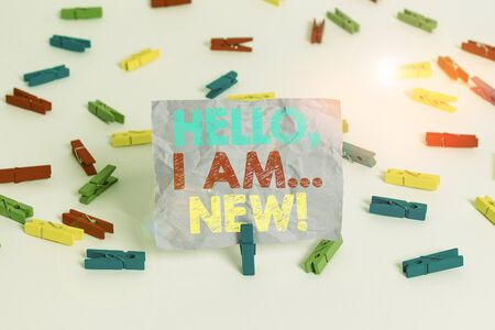 Writing note showing Hello I Am New. Business concept for introducing oneself in a group as fresh worker or student Colored clothespin papers empty reminder white floor background office