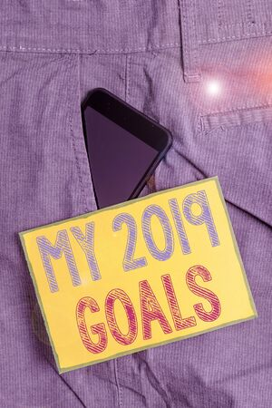 Conceptual hand writing showing My 2019 Goals. Concept meaning setting up demonstratingal goals or plans for the current year Smartphone device inside trousers front pocket note paper
