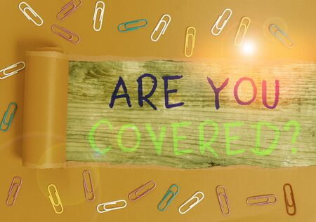 Text sign showing Are You Covered Question. Business photo text asking showing if they had insurance in work or life Paper clip and torn cardboard placed above a wooden classic table backdrop Zdjęcie Seryjne