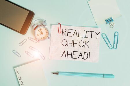 Handwriting text Reality Check Ahead. Conceptual photo makes them recognize truth about situations or difficulties Alarm clock clips notepad smartphone rubber band marker colored background