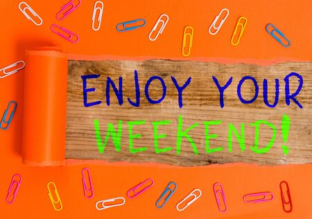 Text sign showing Enjoy Your Weekend. Business photo text wishing someone that something nice will happen at holiday Paper clip and torn cardboard placed above a wooden classic table backdrop