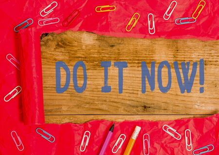 Handwriting text writing Do It Now. Conceptual photo not hesitate and start working or doing stuff right away Stationary and torn cardboard placed above a wooden classic table backdrop Stock fotó