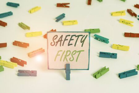Text sign showing Safety First. Business photo text used to say that the most important thing is to be safe Colored clothespin papers empty reminder white floor background office Stock fotó