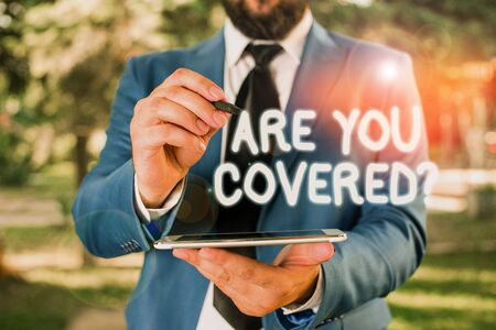 Conceptual hand writing showing Are You Covered Question. Concept meaning asking showing if they had insurance in work or life Businessman in blue suite stands with mobile phone in hands Zdjęcie Seryjne