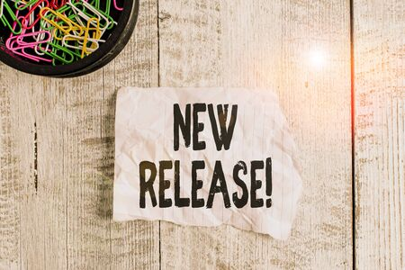 Conceptual hand writing showing New Release. Concept meaning announcing something newsworthy recent product Wrinkle paper and cardboard placed above wooden background