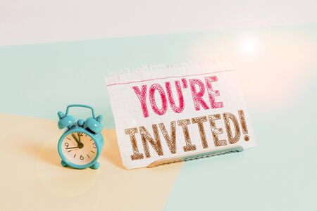 Word writing text You Re Invited. Business photo showcasing make a polite friendly request to someone go somewhere Mini size alarm clock beside a Paper sheet placed tilted on pastel backdrop