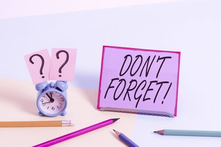 Conceptual hand writing showing Don T Forget. Concept meaning used to remind someone about important fact or detail Mini size alarm clock beside stationary on pastel backdrop
